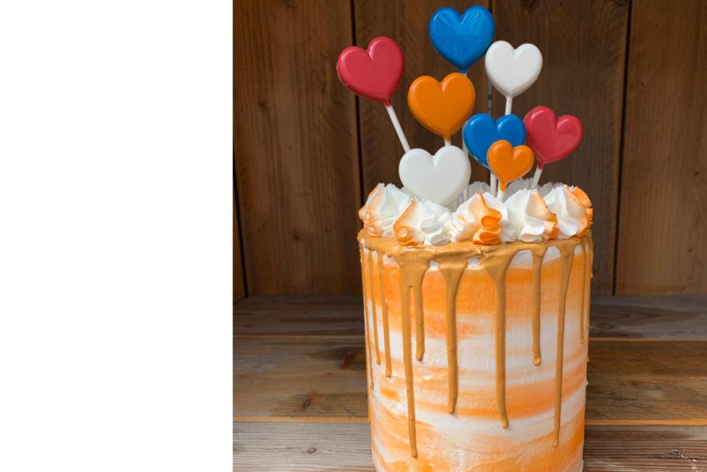 Orange drip cake with heart lollipops